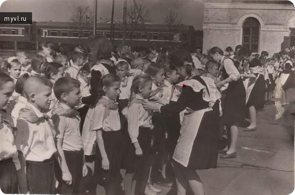 вожатые повязывают пионерские галстуки юным пионерам.